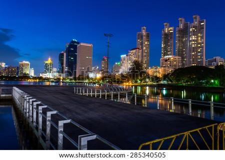 Business buildings in Bangkok seen from Benjakiti park, night Scene, Thailand - stock photo