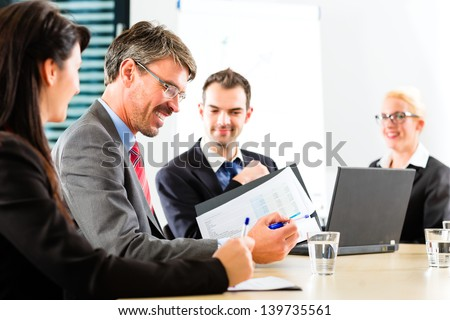 Business - businesspeople have a meeting with presentation in office, they negotiate a contract - stock photo