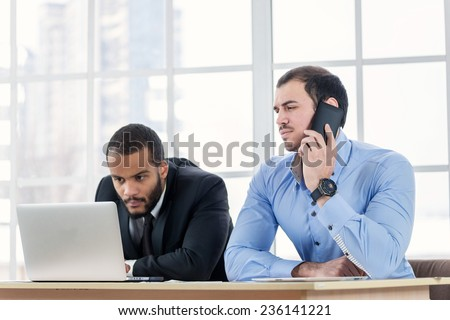 Business call. Confident businessman calling on a cell phone while his colleagues are working at a laptop at his desk in the office in the formal wear. - stock photo