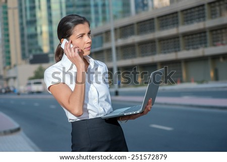 Business call. Successful businesswoman standing in the street in formal attire holding a laptop while talking on cell phone. Arab businessman working on laptop in among the skyscrapers in Dubai - stock photo