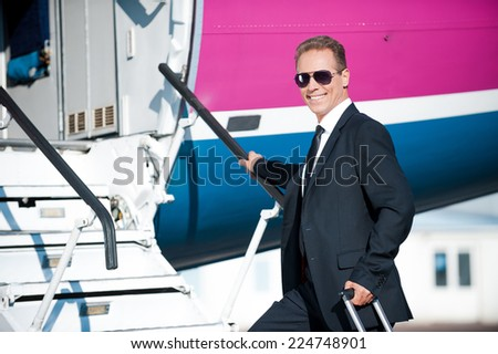 Business calling. Confident mature businessman moving up by airplane ladder to the entrance