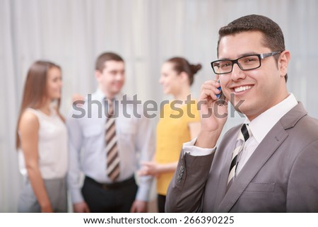 Business calls. Confident handsome businessman talking over the phone with a smile while his colleagues standing in blurry on the background - stock photo