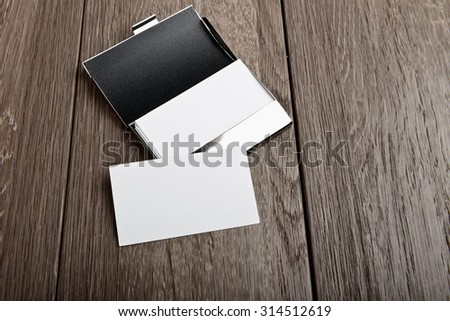Business card and cardholder on wooden table - stock photo