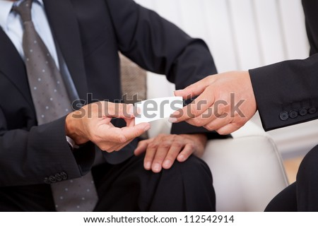 Business card being passed over between a male and female businessperson in suits