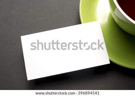Business card blank over coffee cup at office table. Corporate stationery branding mock-up - stock photo