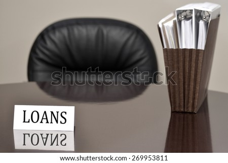 Business card for loans lending on desk with files and chair  - stock photo
