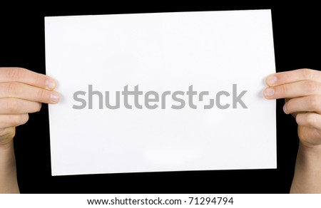 business card in a hand on the black background - stock photo