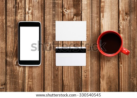 Business card, plastic card and cell phone mock-up on table - stock photo