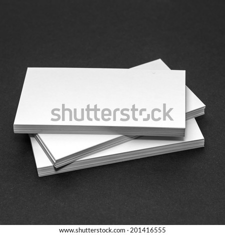 Business card template for branding identity with blank modern devices and modern abstract logo print. Isolated on black paper background. - stock photo
