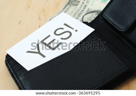 Business card with the sign YES!  in wallet with dollars   - stock photo