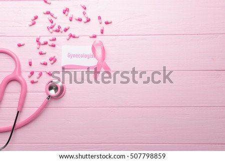 Business card with word GYNECOLOGIST, ribbon and pills on pink wooden background