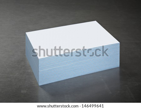 Business Cards Stack on Brushed Steel. Blank with Blue Striped edge. - stock photo