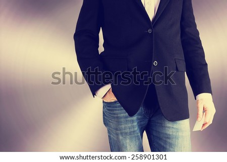 business casual man with a relaxed stance holding a business card with a stainless steel backdrop with a retro instagram filter (shallow depth of field)