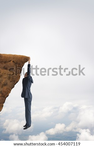 business challenge concept businessman clinging on to a cliff - stock photo