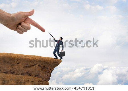 business challenge concept businessman pushed to the edge of a cliff
