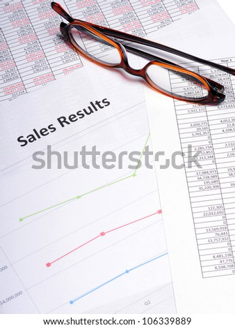 Business Charts and graphs showing sales results with a pair of glasses