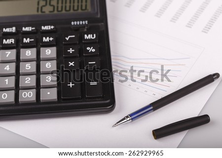 Business Charts with calculator and pen on white background - plan, analyze - stock photo
