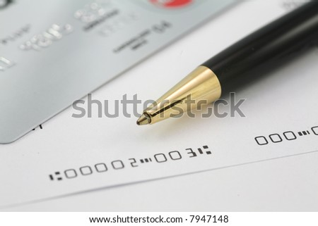 Business check with credit card and pen