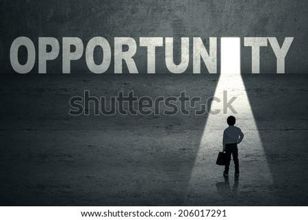 Business child walks toward an opportunity door - stock photo