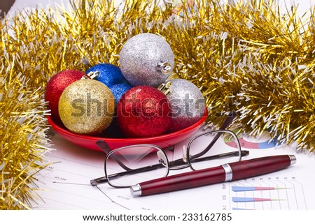 Business Christmas of red balls, pen, spectacles, tinsel, saucer - stock photo