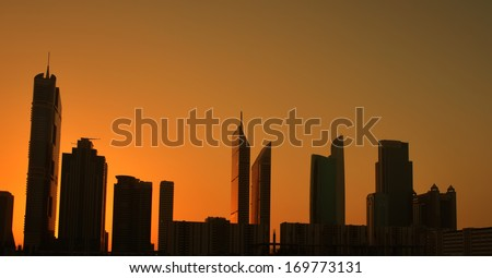 Business city in sunset. Silhouettes of buildings against orange sky. - stock photo