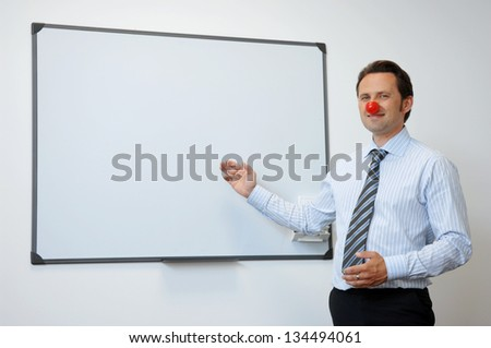 Business Clown With Red Nose Presenting Something On The Board - stock photo