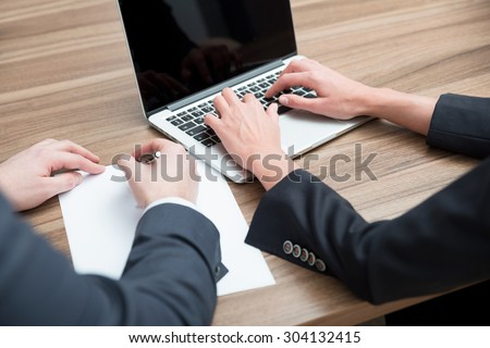 Business colleagues are working on the project. A laptop and a blank paper are on the table. Toning filter. - stock photo