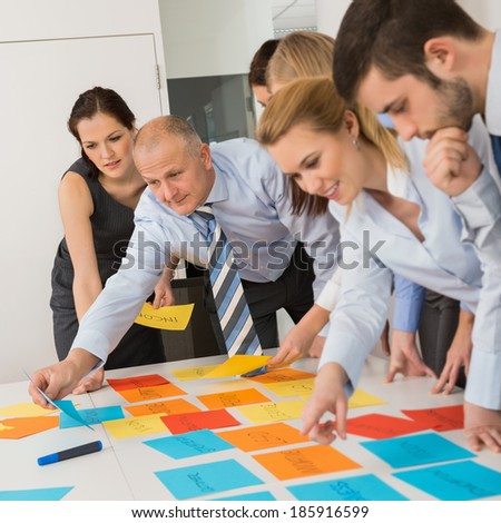 Business colleagues arranging multicolored labels on table in meeting - stock photo