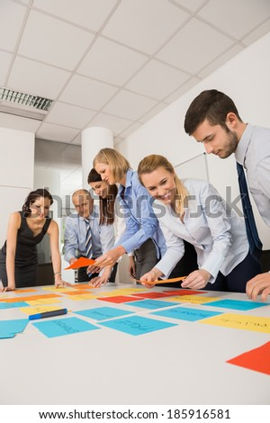 Business colleagues brainstorming with multicolored labels planning strategy in meeting - stock photo