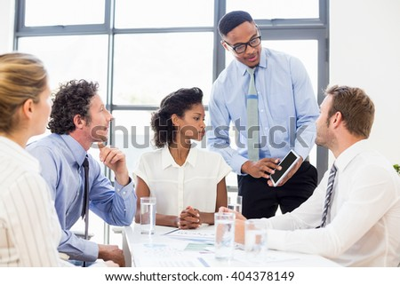 Business colleagues discussing over a tablet in office