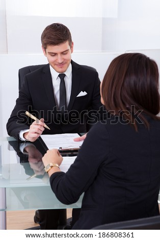 Business colleagues discussing over document in meeting - stock photo