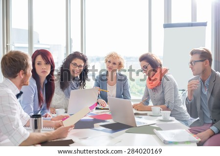 Business colleagues discussing over photographs at conference table in creative office - stock photo