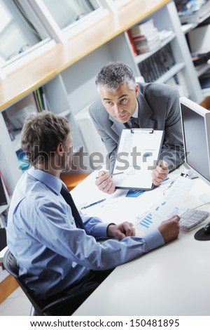 Business colleagues discussing together in an office - stock photo