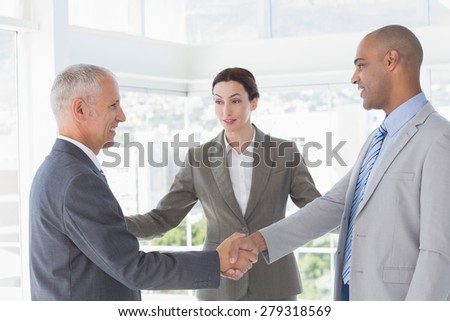 Business colleagues greeting each other in the office - stock photo