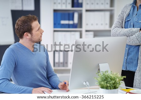 Business colleagues having a serious discussion in the office with focus to a young businessman sitting in his chair looking up at a woman - stock photo