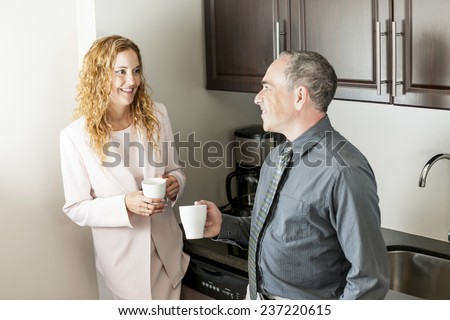Business colleagues having conversation in office coffee break area - stock photo