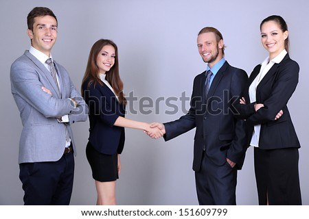 Business colleagues introducing with handshake, on grey background - stock photo
