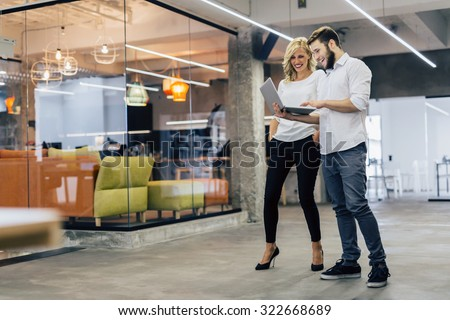 Business colleagues laughing while looking at the laptop - stock photo
