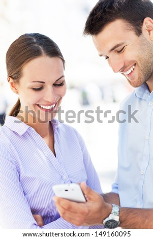 Business colleagues looking at mobile phone - stock photo