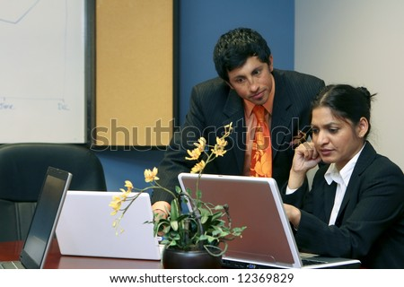Business colleagues looking serious while reviewing a laptop screen in a conference room - stock photo