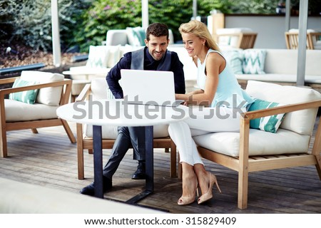 Business colleagues looking to the net-book screen during work break, intelligent people sitting with a laptop in modern cafe, young entrepreneurs met in restaurant to discuss some project together - stock photo