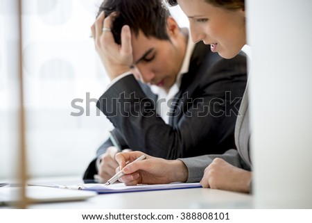 Business colleagues, man and woman, working at office desk reading a report or document looking a bit stressed and agitated. Focus to her hand. - stock photo