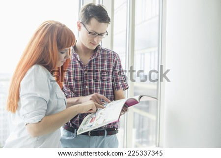 Business colleagues reading file in creative office - stock photo