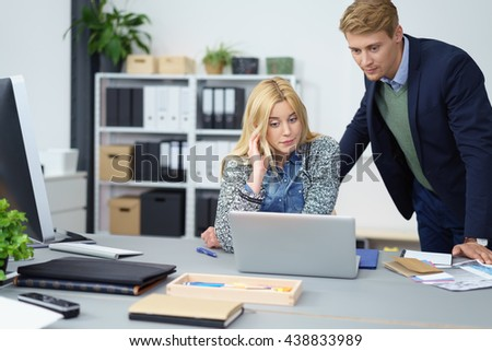 Business colleagues reading online documents together on a laptop computer with serious thoughtful expressions, young man and woman - stock photo