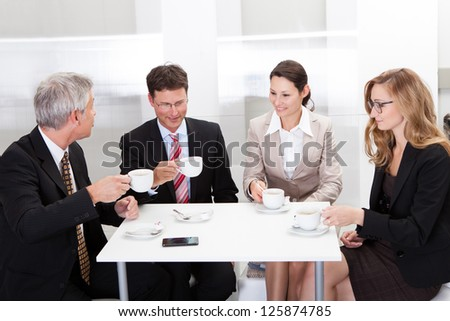 Business colleagues relaxing over coffee or having an impromptu meeting in the cafeteria - stock photo