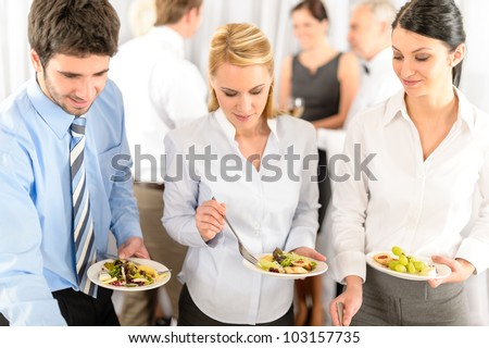 Business colleagues serve themselves at buffet catering service company event - stock photo