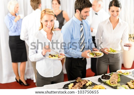 Business colleagues serve themselves at buffet catering service company event