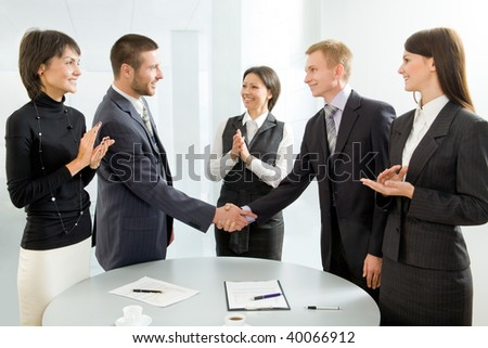 Business colleagues shaking hands and applauding - stock photo