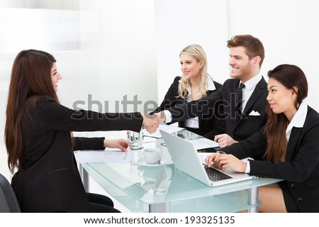 Business colleagues shaking hands at desk in office
