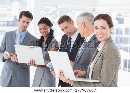 Business colleagues showing their multimedia devices to each other in the office - stock photo